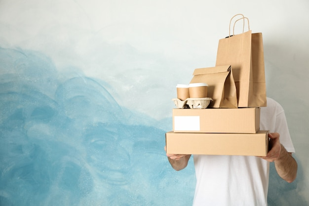 Man holds boxes, coffee cups and paper packages indoor, space for text