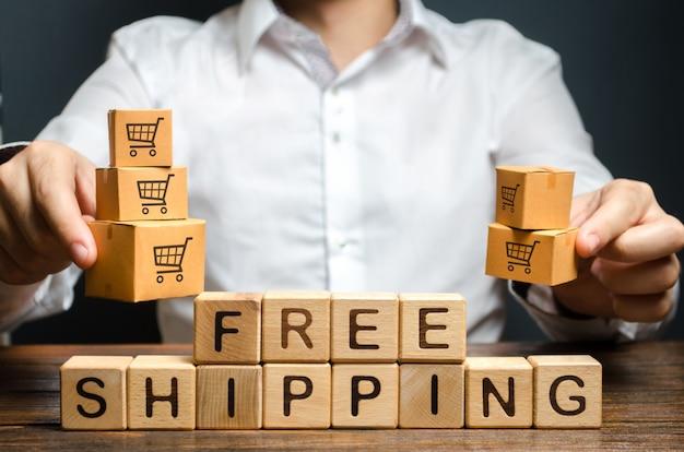 Мужчина держит коробки надписью бесплатная доставка. акции льготные условия для крупных клиентов