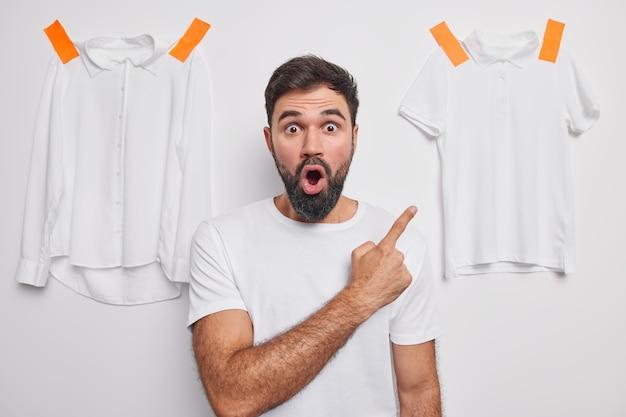 남자는 벽에 회반죽을 칠한 옷에서 숨을 참으며 흰색의 캐주얼 복장을 보여줍니다.