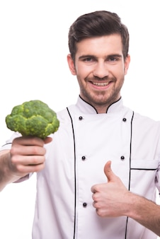 A man holds broccoli in his hand and shows a super sign.