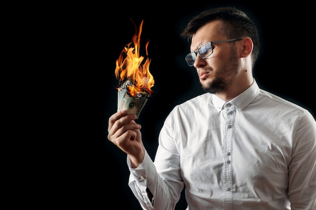 A man holds burning money in his hand