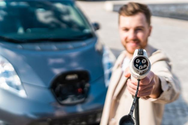 男は電気自動車のバッテリーを充電するためのケーブルを持っています