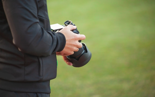 A man holds a camera in his hands on a blurry green background