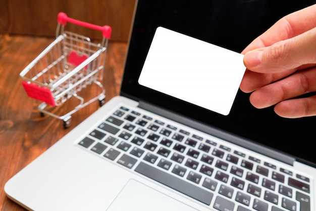 A man holds a card for copy space and mock up against the background of a laptop and a trolley.