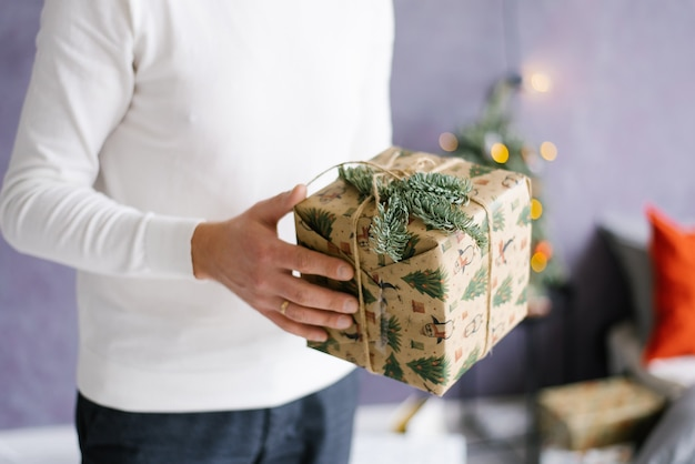 A man holds a christmas or new year gift in his hands.