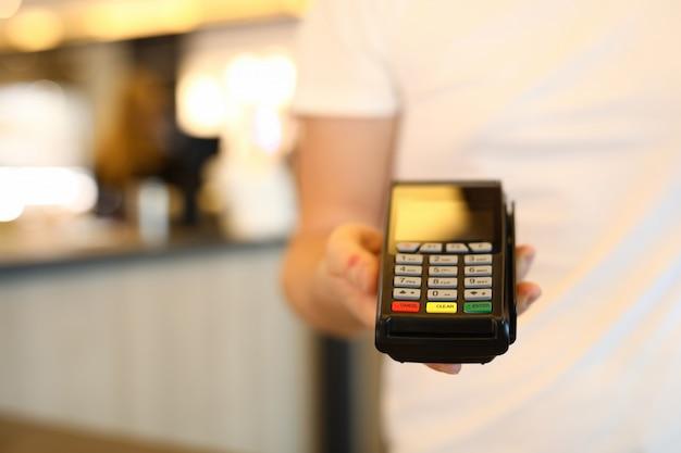 男は商業用携帯銀行端末を保持