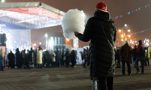 A man holds cotton candy, a child looks at him