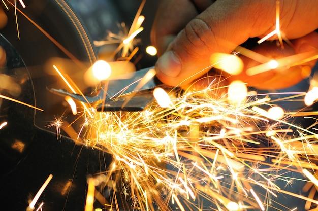 男は手に詳細を保持し、金属を切断するための機器を操作し、明るい炎の火花が飛び散る、クローズアップ写真