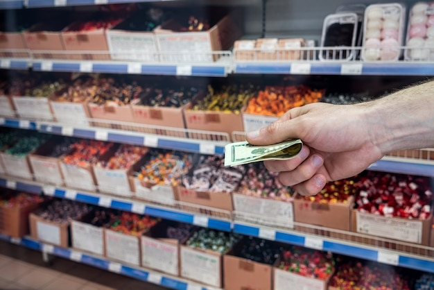 Man holds dollars in the supermarket. purchase concept