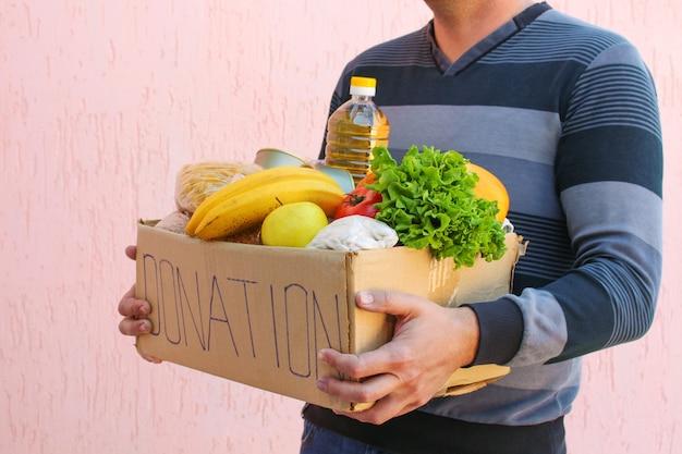 남자는 음식과 함께 기부 상자를 보유하고 있습니다.