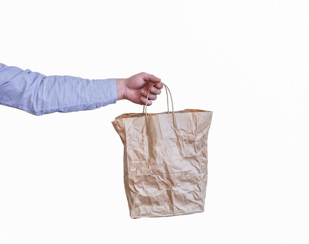 男は白い背景で隔離のクラフト紙からエコバッグを保持します。