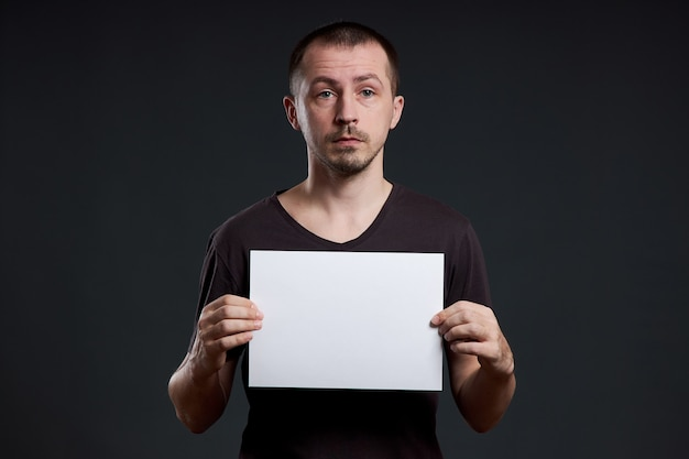 Man holds an empty poster paper sheet in his hands. smile and joy, place for text, copy space