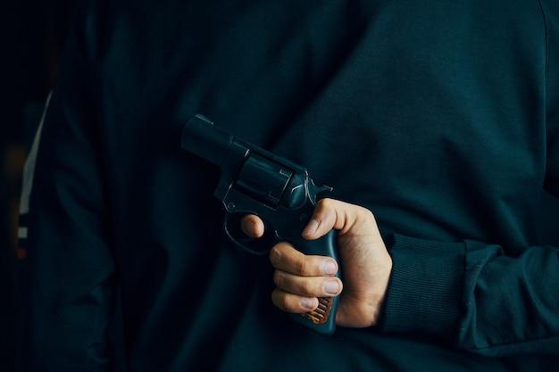 男は男性の手でハンドガンリボルバーで攻撃する準備ができている彼の後ろの人の後ろに銃を持っています