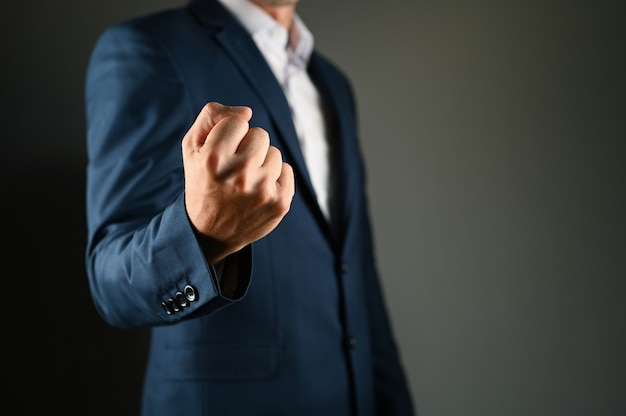 A man holds a fist in front. a man in a suit shows a kuak forward on a black space. concept: strength in business. high quality photo