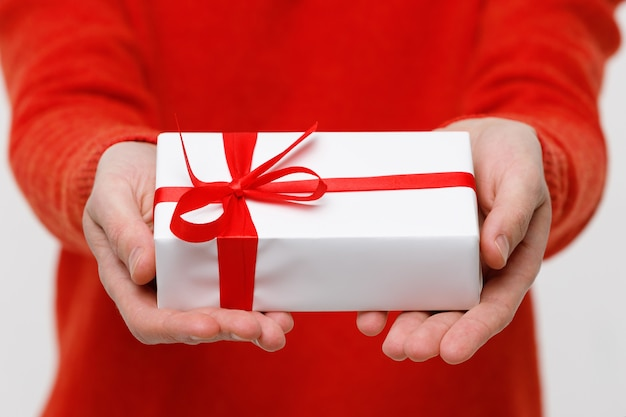 Man holds gift forward in his hand, close up