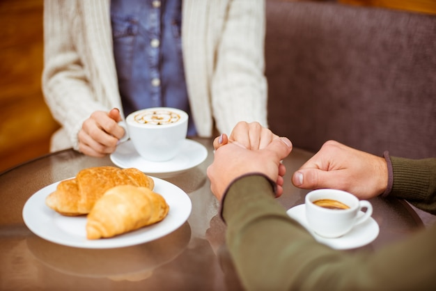 A man holds a girl's hand in a cafe.