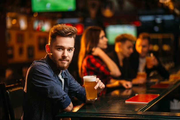 Man holds glass of beer at the bar counter in a sport pub, happy leisure of football fan
