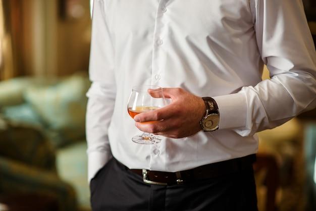 A man holds a glass of cognac