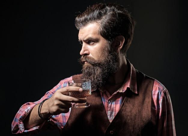 Мужчина держит стакан бренди. роскошный алкогольный напиток. веселый бородатый мужчина пьет дорогой виски на черном.