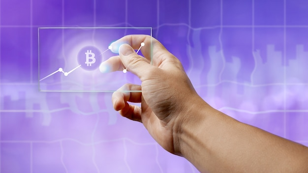 A man holds a glass screen with a bitcoin symbol and a crypto currency graph