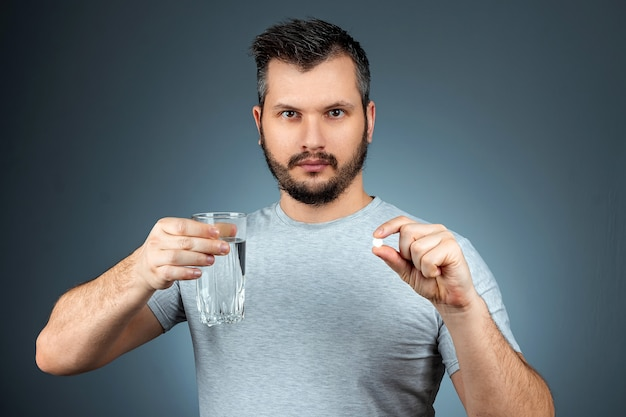 A man holds a glass of water and a pill, taking medication, treatment, gray wall. medical theme, vitamins, health care.