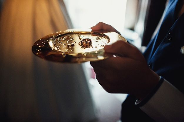 Man holds golden plate with wedding rings in church