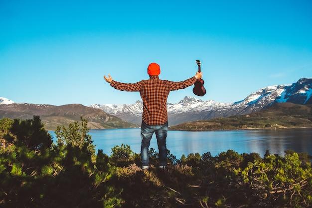 남자는 셔츠를 입은 산 숲과 호수를 배경으로 기타를 들고 있다