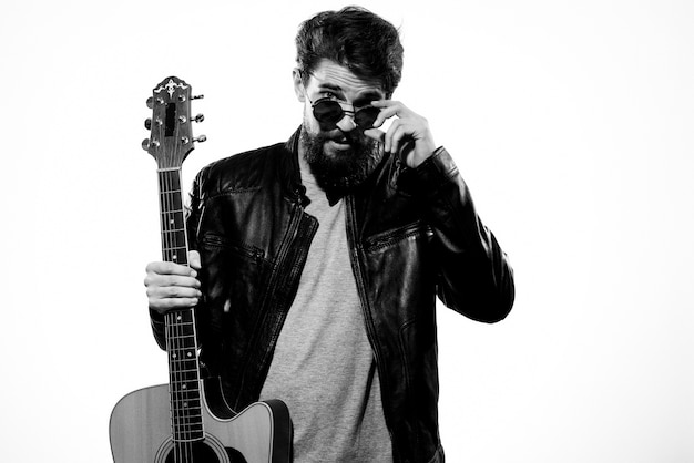 A man holds a guitar in his hands wearing a black leather jacket and dark glasses