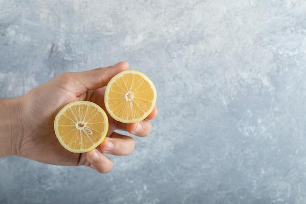 남자는 절반 잘라 신선한 육즙 레몬을 보유하고 있습니다. 고품질 사진