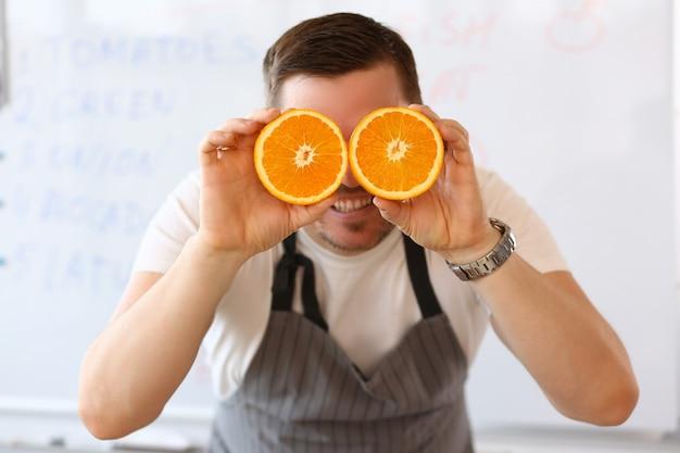 Man holds halves of cut orange as eye
