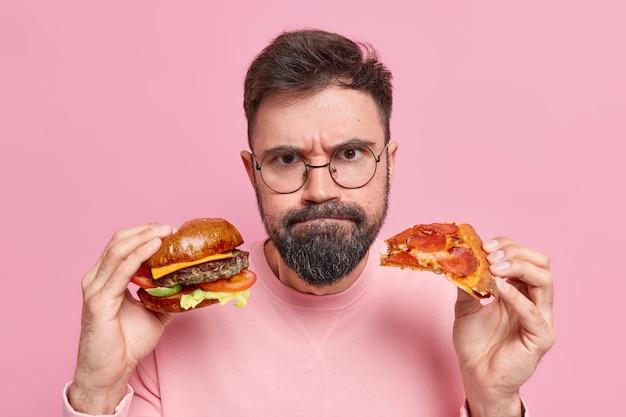 L'uomo tiene l'hamburger e la pizza preme le labbra indossa un maglione con occhiali rotondi