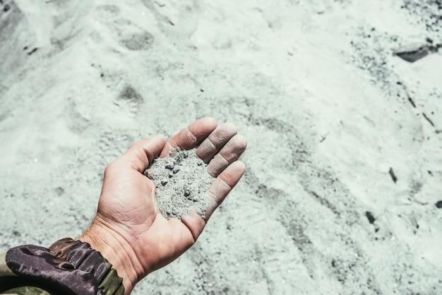 남자는 흐릿한 모래 배경에 빛나는 모래 한 줌을 손에 들고 있습니다. 햇빛에 작은 돌이 있는 소수의 아름다운 흰색 회색 모래가 있는 인간의 손바닥. 작은 결정체와 광물을 손에 들고 있는 남자.