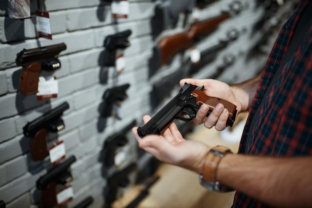 남자는 총기 상점에서 권총을 보유하고 있습니다. 무기 상점에서 보안을 위해 권총을 사는 남성 사람