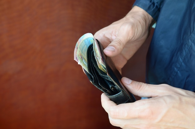 Man holds in hands black leather wallet with ukrainian money or thief who stole wallet full of money