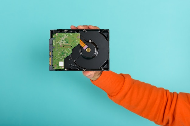 Man holds an hard disk. concept of storage and memory on cyan