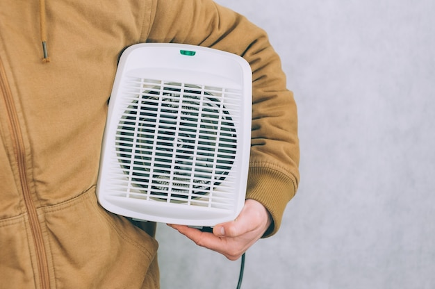 A man holds a heater in his hands on a light.
