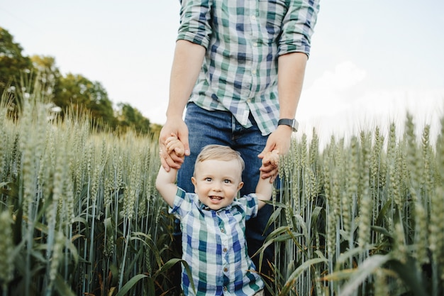 Man holds her son for hands among the wheat field