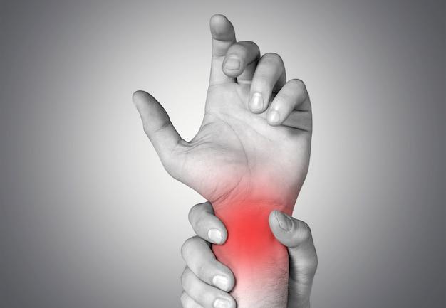 男は手首に彼の手の急性の痛みを保持します