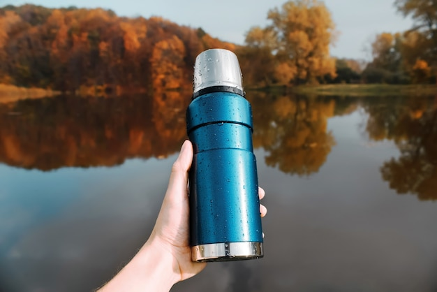 A man holds in his hand a blue thermos, of the autumn forest and lake.