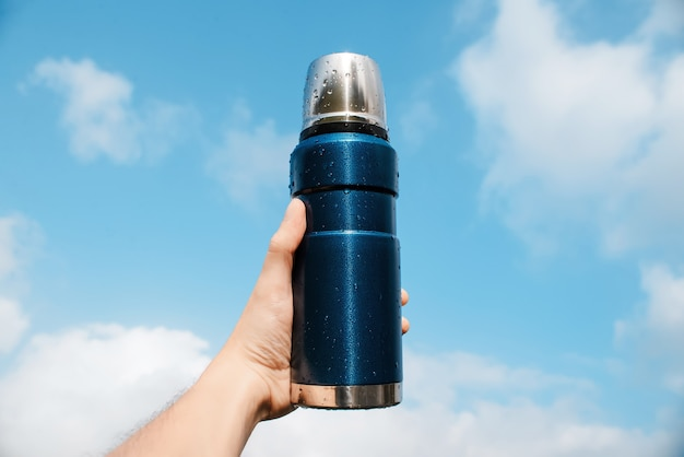 A man holds in his hand a blue thermos, blue cloudy sky.