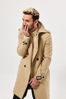 男は彼の顔に手を握るファッショナブルな髪型秋のスタイルのコートファッション