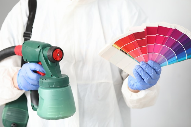 Man holds in his hands spray gun and palette of colors.
