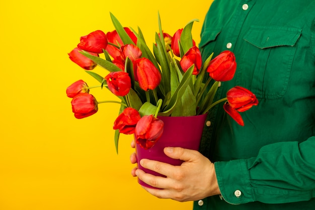 A man holds in his hands a vase with a bouquet of tulips