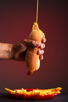 A man holds a hot dog with his hand. mustard drips onto a hot-dog, red background