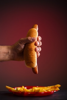 A man holds a hot dog with his hand, red background
