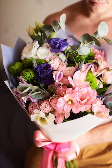 A man holds a huge bouquet of beautiful flowers