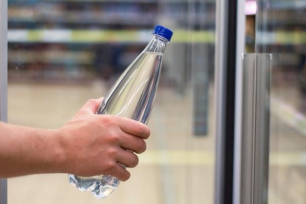 남자는 상점 창 배경에 순수한 미네랄 워터가 든 플라스틱 병을 손에 들고 있습니다.
