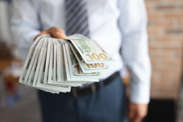 男は100ドル紙幣の彼の手のファンで保持します