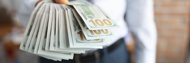 남자는 100 달러 지폐의 그의 손 팬에 보유