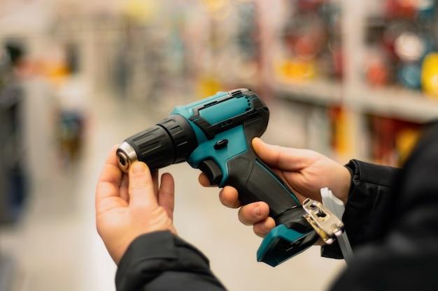 Мужчина держит в руках зеленую аккумуляторную отвертку для ремонтных работ на фоне витрин в строительном магазине.